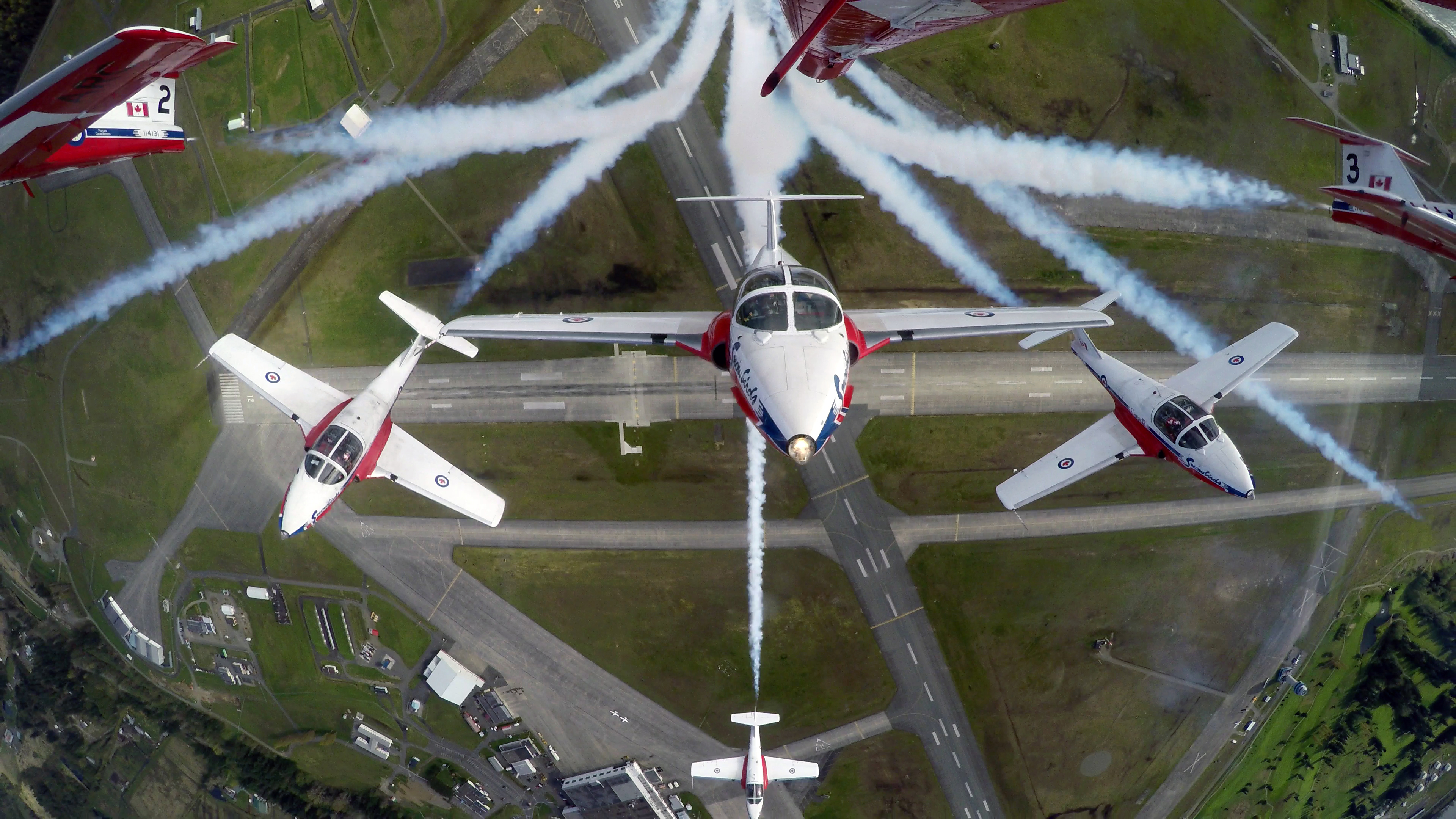 """The Canadian Forces Snowbirds air demonstration team breaking into the """"Canada Burst"""" during their spring training at 19 Wing Comox, British Columbia, in April 2015, is captured by the TankCam installed in a modified smoke tank mounted on the belly of the team leader's CT-114 Tutor aircraft. The tank holds three high-performance cameras able to capture video and imagery of the entire formation in flight. PHOTO: DND"""